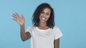 Mão de ondulação da menina africana a dar boas-vindas isolado no fundo azul filme