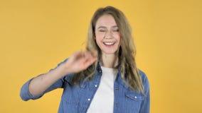 Mão de ondulação da menina bonita nova a dar boas-vindas no fundo amarelo vídeos de arquivo