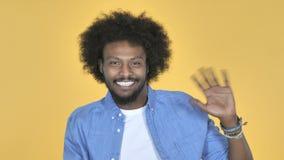 Mão de ondulação do homem afro-americano a dar boas-vindas no fundo amarelo filme
