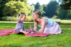 Mão de ondulação do rapaz pequeno acima com a mãe no parque Imagem de Stock