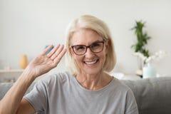 Mão de ondulação envelhecida média de sorriso da mulher que olha a câmera, portrai foto de stock