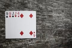 Mão de pôquer: dois pares Cartões de jogo na tabela de madeira Fotos de Stock