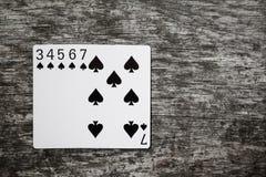 Mão de pôquer: resplendor reto sumário do jogo de cartões do jogo na tabela de madeira Foto de Stock
