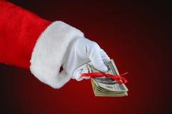 Mão de Papai Noel com dinheiro Fotografia de Stock Royalty Free