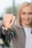 Mão de Saleswomans que agarra as chaves do carro Foto de Stock