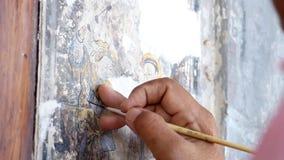 A mão de um artista da pintura está reparando uma pintura chinesa Renovação da pintura chinesa nas paredes de construções velhas vídeos de arquivo