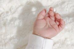 Mão de um bebê no veludo branco fotografia de stock