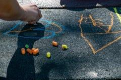 Mão de um desenho da criança com o giz colorido no sol em um assoalho preto textured imagem de stock