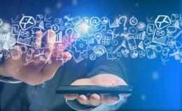 Mão de um dispositivo de terra arrendada do homem com ícones do Internet toda ao redor Foto de Stock