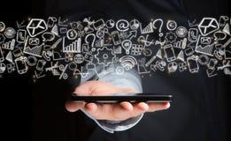 Mão de um dispositivo de terra arrendada do homem com ícones do Internet toda ao redor Foto de Stock Royalty Free