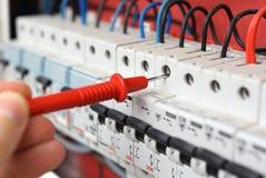 Mão de um eletricista com ponta de prova do multímetro em um interruptor bonde Fotos de Stock Royalty Free