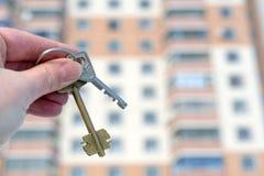 A mão de um homem branco guarda as chaves no fundo de um a Foto de Stock Royalty Free