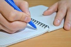 A mão de um homem em uma camisa branca escreve o texto com uma pena azul em um caderno na tabela, guardando a folha com mão foto de stock