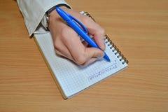 A mão de um homem em uma camisa e em um relógio brancos escreve a prescrição do texto em um caderno em uma opinião de tampo da me foto de stock