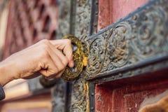 A mão de um homem guarda uma chave do vintage e gerencie-a na fechadura da porta imagens de stock