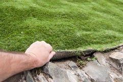 A mão de um homem levanta uma tampa artificial da grama Fotografia de Stock Royalty Free
