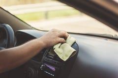 A mão de um homem limpa um tapete com um pano em um matiz retro Imagem de Stock