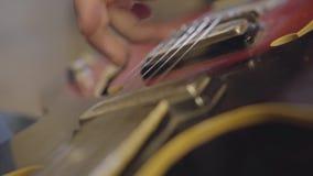 A mão de um homem não reconhecido que joga as cordas de um close-up da guitarra video estoque