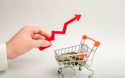 Mão de um homem de negócios com uma seta vermelha que aponta acima sobre um carrinho de mão com moedas conceito do crescimento ec imagem de stock