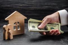 A mão de um homem de negócios estende o dinheiro às figuras de madeira da família e a uma casa de madeira O conceito de comprar e fotos de stock royalty free