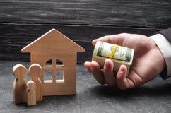 A mão de um homem de negócios estende o dinheiro a uma casa de madeira imagens de stock