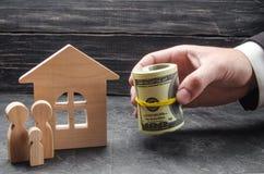 A mão de um homem de negócios estende o dinheiro a uma casa de madeira A família está estando perto da casa O conceito da compra  imagem de stock