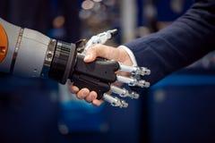 Mão de um homem de negócios que agita as mãos com um robô de Android Imagens de Stock