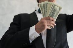 A mão de um homem de negócios que guarda o dinheiro é bem sucedida no negócio, w imagem de stock royalty free