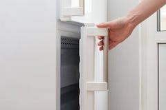 A mão de um homem novo está abrindo uma porta do congelador Fotografia de Stock Royalty Free