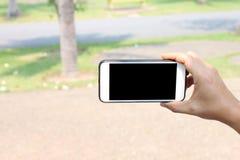 Mão de um homem que guarda Smartphone para o selfie no jardim e no ha imagens de stock
