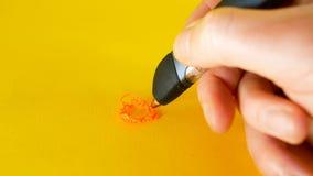 A mão de um homem tira com uma pena em um fundo amarelo, ideal da impressora 3d da metragem para assuntos tais como a inovação, t video estoque