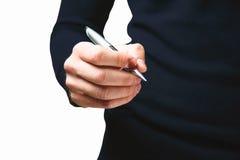 Mão de um indivíduo novo em uma obscuridade - camiseta azul com uma pena do metal em h Imagens de Stock