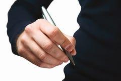Mão de um indivíduo novo em uma obscuridade - camiseta azul com uma pena do metal em h Imagem de Stock