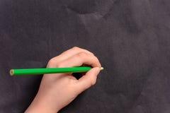 A mão de um rapaz pequeno escreve um lápis em um fundo preto imagens de stock
