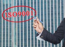 a mão de um uso do homem de negócio uma pena escreve o sistema de texto ISO 9001 Imagens de Stock