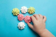 A mão de uma criança alcança para a merengue pairosa, multi-colorida doce em um fundo azul O conceito de um feriado, uma criança imagem de stock royalty free