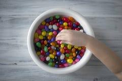 A mão de uma criança que pegara doces de uma placa branca imagem de stock