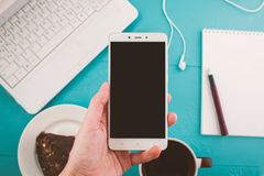 Mão de uma menina com um telefone, desktop com um portátil, espaço para o texto Fotos de Stock Royalty Free