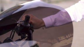 Mão de uma menina na camisa branca no regulador de pressão do aperto de torção da motocicleta, gás de gerencio sobre filme