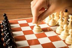 A mão de uma menina que joga a xadrez Fim acima fotos de stock royalty free