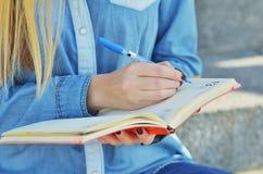 A mão de uma moça vestida em uma camisa da sarja de Nimes, que escreva em um caderno na rua fotos de stock
