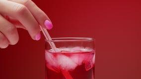 A mão de uma mulher agita cubos de gelo em um vidro do gelo e da água de soda vermelha com gás Fundo vermelho Conceito da bebida  filme