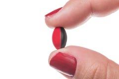 Mão de uma mulher com os pregos vermelhos que mantêm um fim do comprimido da cápsula isolado acima no fundo branco foto de stock royalty free