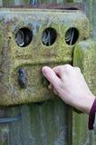 A mão de uma mulher das pessoas idosas comuta a eletricidade em uma oxidação velha Fotografia de Stock Royalty Free