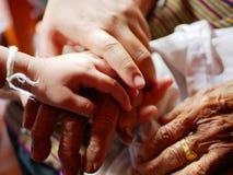 Mão de uma mulher nas mãos de suas filha e mãe idosa - ligação de família fotografia de stock