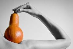 A mão de uma mulher prende a abóbora Foto de Stock Royalty Free