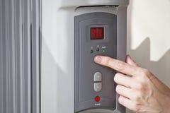 A mão de uma mulher que ajusta a temperatura ambiente em um calefator de óleo programável digital Foto de Stock