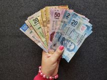 mão de uma mulher que guarda cédulas mexicanas de denominações diferentes imagem de stock royalty free
