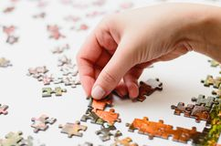 Mão de uma mulher que joga o enigma de serra de vaivém, começando combinar a torta Imagens de Stock