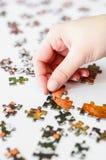 Mão de uma mulher que joga o enigma de serra de vaivém, começando combinar a torta Imagem de Stock Royalty Free